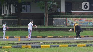 Murid berolahraga saat mengikuti Drive in Learning (DRIL) dengan konsep pembelajaran di ruang terbuka di Jakarta, Senin (5/4/2021). Kegiatan tersebut dilakukan guna menghidupkan semangat belajar siswa dengan tetap mengikuti protokol kesehatan secara ketat. (Liputan6.com/Herman Zakharia)