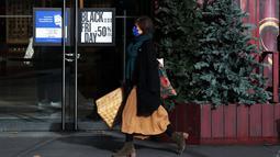 """Seorang perempuan berjalan melewati poster """"Black Friday"""" di Paris, Prancis, pada 4 Desember 2020. Sempat ditunda selama sepekan akibat karantina wilayah (lockdown) nasional, pesta belanja tahunan """"Black Friday"""" di Prancis akhirnya dimulai pada Jumat (4/12). (Xinhua/Gao Jing)"""