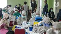 Suasana vaksinasi COVID-19 kepada pedagang di Pasar Induk Kramat Jati, Jakarta Timur, Selasa (9/3/2021). Penyuntikan vaksin tahap pertama ini menargetkan 1.000 peserta. (Liputan6.com/Faizal Fanani)