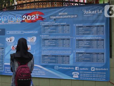 Orang tua murid mencari informasi pengajuan akun untuk mengikuti proses penerimaan Peserta Didik Baru (PPDB) Tahun Pelajaran 2021/2022 di SMA Negeri 87 Jakarta, Senin (7/6/2021).  (Liputan6.com/Herman Zakharia)