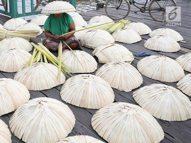 Perajin membuat caping khas Banjar di kawasan Pasar Apung Kuin, Kalimantan Selatan, Senin (26/3). Caping yang disebut tanggui oleh masyarakat Banjar tersebut merupakan topi tradisional khas Banjar. (Liputan6.com/Immanuel Antonius)