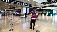 "Petugas mengenakan termoscanner portabel ""Smart-Helmet"" untuk memeriksa suhu penumpang dan sesama staf di terminal keberangkatan bandara Fiumicino Roma, Italia pada 5 Mei 2020. Hal ini dilakukan guna menyaring orang yang memiliki gejala infeksi virus corona. (ANDREAS SOLARO/AFP)"