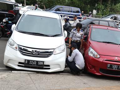 Petugas menderek dan menggembosi ban mobil yang parkir sembarangan di kawasan Tebet, Jakarta, Kamis (28/3). Meskipun berulang kali ditertibakan, namun masih banyak pengendara yang nekat parkir sembarangan sehingga mengganggu arus lalu lintas. (Liputan6.com/Immanuel Antonius)