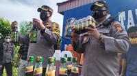 Kepala Polresta Pekanbaru dan Kepala Polsek Tampan memegang barang bukti jamu ilegal. (Liputan6.com/M Syukur)