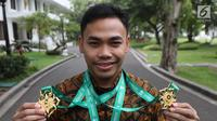Lifter Indonesia, Eko Yuli Irawan menunjukkan medali di Istana Merdeka, Jakarta (8/11). Eko memecahkan rekor dunia untuk total angkatan 317 kg dan angkatan clean and jerk 174 kg di kejuaraan dunia angkat besi di Turkmenistan. (Liputan6.com/Angga Yuniar)