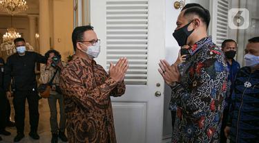 Gubernur DKI Jakarta Anies Baswedan (kiri) memberi isyarat salam kepada Ketua Umum Partai Demokrat Agus Harimurti Yudhoyono atau AHY (kanan) saat menerima kunjungannya di Balai Kota DKI Jakarta, Kamis (6/5/2021). Kunjungan AHY untuk silaturahmi dan membicarakan Jakarta. (Liputan6.com/Faizal Fanani)