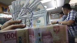 Teller menunjukkan uang dolar dan rupiah di penukaran uang di Jakarta, Junat (23/11). Nilai tukar dolar AS terpantau terus melemah terhadap rupiah hingga ke level Rp 14.504. (Liputan6.com/Angga Yuniar)