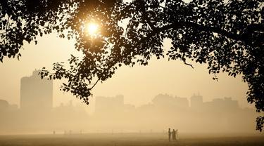 Orang-orang berjalan di pagi berkabut di taman Maidan di Kolkata (29/11/2019). Selama musim dingin, wilayah utara India sering mengalami kabut tebal, menyebabkan penundaan lalu lintas dan mengganggu jadwal penerbangan dan kereta api. (AFP Photo/Dibyangshu Sarkar)
