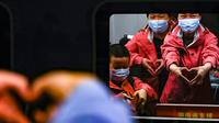 Staf medis dari Provinsi Hunan memberi isyarat ucapan selamat tinggal di dalam kereta di Stasiun Kereta Api Wuhan di Provinsi Hubei, China (17/3/2020). Beberapa tim bantuan medis  mulai meninggalkan Hubei ketika epidemi COVID-19 yang terkena dampak paling parah itu terus menurun. (Xinhua/Shen Bohan)