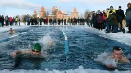 Suasana kompetisi renang musim dingin tahunan dengan air es beku di Trakai, Lituania (24/2). Para peserta tetap antusias mengikuti lomba walaupun dengan suhu di luar hingga minus 12 derajat Celcius. (AFP Photo/Petras Malukas)