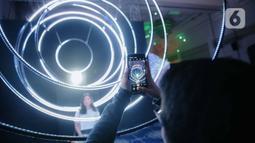 Pengunjung berpose saat mengunjungi pameran seni berbasis teknologi berwujud sorotan cahaya futuristik 'Wave of Tomorrow' di Jakarta, Sabtu (21/12/2019). Di mana karya seni tersebut menyoroti yang terjadi di masa kini dan memprediksi apa yang akan terjadi di masa depan. (Liputan6.com/Faizal Fanani)