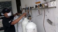 Pekerja menyiapkan pengisian ulang tabung oksigen di UD Berkah Oksigen, Kota Depok, Jawa Barat, Jumat (6/8/2021). Yayasan Khadimul Ummah Madani bekerjasama dengan UD Berkah Oksigen menyelenggarakan isi ulang tabung oksigen gratis setiap Jumat pukul 08.00-17.00 WIB. (Liputan6.com/Helmi Fithriansyah)