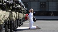 Seorang wanita berlutut di depan barisan polisi antihuru-hara saat mereka memblokir demonstrasi pendukung oposisi Belarusia di Minsk, Belarusia, Minggu (30/8/2020). Puluhan ribu demonstran berkumpul untuk menuntut agar Presiden Belarusia Alexander Lukashenko mengundurkan diri. (AP Photo)