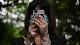 Seorang warga mengenakan masker dan sarung tangan menunggu dalam barisan untuk tes virus corona di lingkungan di Wuhan, provinsi Hubei, Jumat (15/5/2020). Pihak berwenang Kota Wuhan menggelar tes massal terhadap 11 juta warganya untuk mencegah gelombang kedua pandemi Covid-19. (Hector RETAMAL/AFP)
