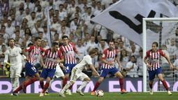 Gelandang Real Madrid, Luka Modric, berusaha melewati kepungan pemain Atletico Madrid pada laga La liga di Stadion Santiago Bernabeu, Madrid, Sabtu (29/9/2018). Kedua klub bermain imbang 0-0. (AFP/Oscar Del Pozo)