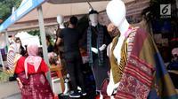 Pengunjung melihat-lihat produk kain tenun yang dipamerkan di Festival Sarung Indonesia 2019, Plaza Tenggara Kompleks GBK, Jakarta, Minggu (3/3). Festival ini diikuti sejumlah perajin sarung tenun dari berbagai daerah. (Liputan6.com/Helmi Fithriansyah)
