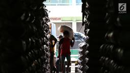 Seorang kuli angkut memanggul beras di Pasar Induk Cipinang, Jakarta, Senin (25/9). Penetapan HET beras kualitas medium zona Jawa, Lampung, Sumatera Selatan, Bali, NTB dan Sulawesi Rp 9.450/kg dan Rp 12.800 untuk beras premium (Liputan6.com/Angga Yuniar)