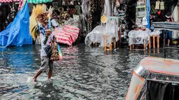 Seorang penjual sapu berjalan melewati banjir di tengah hujan deras yang tiba-tiba mengguyur di sebuah pasar dekorasi Natal di Manila, Filipina (9/12/2020). (Xinhua/Rouelle Umali)