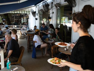 Seorang pramusaji menyajikan makanan di sebuah restoran di Tel Aviv, Israel pada Rabu (27/5/2020). Setelah lebih dari dua bulan ditutup untuk membendung penularan virus corona, restoran hingga kafe di Israel diizinkan dibuka kembali hari Rabu, 27 Mei. (AP Photo/Sebastian Scheiner)