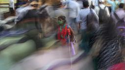Seorang perempuan meminta sedekah saat orang-orang bergegas menaiki kereta di luar terminal kereta Chhatrapati Shivaji Maharaj di Mumbai, India,  9 November 2020. Penghitungan kasus virus corona terkonfirmasi di India, terbesar kedua di dunia, lebih dari 8,5 juta. (AP Photo/Rafiq Maqbool)