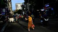 Seorang perempuan menyeberang jalan sebelum hujan lebat mengguyur Hanoi, ibu kota Vietnam pada 11 Agustus 2020. Setelah mencatat nol kasus COVID-19 selama lebih dari tiga bulan, Vietnam melaporkan sejumlah infeksi baru di dalam negeri sejak akhir Juli. (MANAN VATSYAYANA/AFP)