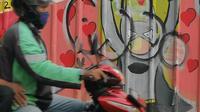 Pengendara melintasi mural yang menghiasi tembok di kawasan Margonda, Depok, Sabtu (16/2). Gambar mural memiliki pesan agar masyarakat tetap damai dan berteman meski berbeda dalam memilih calon presiden dalam Pilpres 2019. (Liputan6.com/Herman Zakharia)