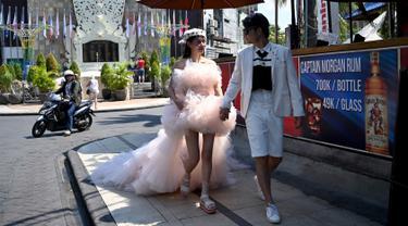 Suami istri berpose untuk foto pre-wedding di seberang jalan Monumen Ground Zero Bali untuk memperingati tragedi bom Bali 2002 di Kuta, Bali (11/10/2019). Bom Bali 2002 merupakan rangkaian tiga peristiwa pengeboman yang terjadi pada malam hari tanggal 12 Oktober 2002. (AFP Photo/Sonny Tumbelaka)