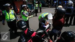 Polisi mengisi surat tilang untuk pengendara motor pada Operasi Progo Patuh di Jl Malioboro, Yogyakarta, Rabu (18/5). Operasi Patuh di gelar secara serempak di seluruh Indonesia hingga 29 Mei 2016. (Liputan6.com/Boy Harjanto)