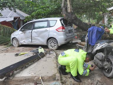 Petugas polisi lalu lintas dari Polres pandeglang melakukan identifikasi kendaraan motor  yang rusak akibat terjangan tsunami di Tanjung Lesung Beach Club, Pandeglang, Banten, selasa (25/12). (Merdeka.com/Arie Basuki)