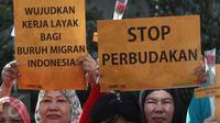Pekerja Rumah Tangga Migran (PRT Migran) yang tergabung dalam Migrant Care membentangkan poster saat aksi damai di kawasan Bundaran HI, Jakarta, Minggu (18/12). Aksi tersebut memperingati Hari Migran Internasional 2016. (Liputan6.com/Immanuel Antonius)