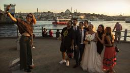 Wisatawan dari Iran berswafoto di Jembatan Galata di atas Tanduk Emas di Istanbul (26/7/2019). Sampai 1980-an Tanduk Emas merupakan tanah tempat pembuangan limbah industri, tetapi sejak setelah dibersihkan merupakan daya tarik wisata yang terkenal di Istanbul. (AP Photo/Emrah Gurel)
