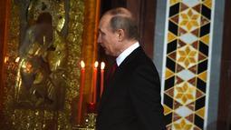 Presiden Rusia, Vladimir Putin saat mengikuti prosesi Paskah Ortodoks di Gereja Katedral Kristus Juru Selamat di Moskow, Rusia,(16/4). (AFP Photo / Vasily Maximov)