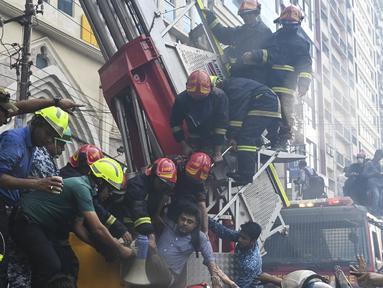 Petugas pemadam kebakaran Bangladesh menyelamatkan seorang pria dari gedung kantor yang terbakar di Dhaka (28/3). Kebakaran besar melanda gedung perkantoran yang menewaskan sedikitnya lima orang dan lainnya masih terperangkap dalam gedung yang terbakar tersebut. (AFP/Munir Uzzaman)