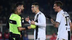 Pemain Juventus, Cristiano Ronaldo berdebat dengan wasit saat melawan Torino dalam Serie A Italia di Stadion Olimpiade, Turin, Italia, Sabtu (15/12). Juventus menjadi satu-satunya klub yang sudah mampu membuat 5.000 gol di Serie A. (Marco BERTORELLO/AFP)