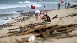 Turis bersantai menikmati Pantai Kuta yang dikelilingi oleh puing-puing dan sampah di Bali, Minggu (9/12). Kawasan pantai Kuta kembali dipenuhi oleh sampah hanyut terbawa oleh gelombang. (SONNY TUMBELAKA / AFP)