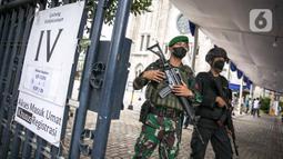 Anggota TNI dan Polisi bersenjata lengkap melakukan penjagaan di gerbang masuk Gereja Katedral, Jakarta, Kamis (1/4/2021). Sebanyak 150 personel gabungan TNI, Polri dan Satpol PP melakukan pengamanan jelang rangkaian perayaan Hari Paskah di gereja tersebut. (Liputan6.com/Faizal Fanani)