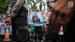 Massa membawa gambar warga Kashmr yang menjadi korban kekerasan dalam aksi solidaritas di depan Kedubes India, Jakarta, Rabu (6/2). Massa meminta pemerintah India segera menghentikan genosida yang dilakukan oleh militer. (Liputan6.com/Faizal Fanani)