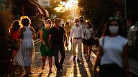 Turis yang mengenakan masker untuk melindungi dari penyebaran virus corona berjalan di kota Ayvalik di Laut Aegea, Turki, Rabu (9/9/2020). Turki telah mewajibkan penggunaan masker di semua lokasi selain di rumah, menyusul lonjakan jumlah infeksi COVID-19. (AP Photo/Emrah Gurel)