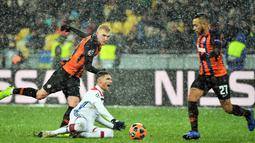 Bek Shakhtar Donetsk, Serhiy Kryvtsov (kiri) dan gelandang Olympique Lyon Houssem Aouar (tngah) berebut bola saat bermain pada penyisihan Grup F Liga Champions di Stadion NSK Olimpiyskyi, Kiev, Ukraina, Rabu (12/12). (SERGEI SUPINSKY/AFP)