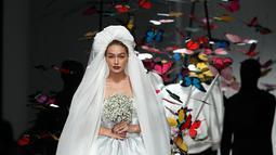 Gigi Hadid berjalan di runway mengenakan gaun rumah mode Moschino untuk koleksi SS19 selama gelaran fashion week di Milan, Italia, Kamis (20/9). Gigi tampil dalam balutan gaun pengantin berpotongan pendek dengan desain menggelembung. (AP/Antonio Calanni)