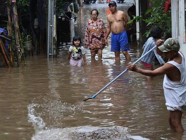 Warga membersihkan banjir yang menggenangi kawasan Cilandak Timur, Jakarta Selatan, Selasa (22/1). Hujan deras yang mengguyur Jakarta dan sekitarnya sejak pagi menyebabkan banjir di sejumlah sudut Ibu Kota. (Liputan6.com/Immanuel Antonius)