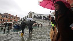 Warga berjalan dekat Jembatan Rialto saat gelombang pasang menerjang  di Venesia, Italia, Selasa (12/11/2019). Venesia dilanda banjir akibat gelombang pasang setinggi 127 cm. (AP Photo/Luca Bruno)
