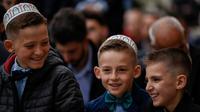 Anak-anak muslim bercanda usai melaksanakan salat Idul Fitri di Masjid Agung Pristina, Kosovo, Selasa (4/6/ 2019). Selain Kosovo, sejumlah negara juga merayakan Hari Raya Idul Fitri hari ini. (Armend NIMANI/AFP)