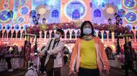 Pengunjung mengenakan masker saat mereka berjalan di luar resor hotel kasino Venesia di Macau, yang pada 22 Januari melaporkan kasus pertama dari Virus Corona Baru. (source: AFP)