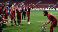 Bintang Liverpool, Mohammed Salah berfoto dengan trofi Liga Champions setelah kemenangan 2-0 atas Tottenham Hotspur pada final di Wanda Metropolitano, Minggu (2/6/2019) dini hari WIB. (AFP/Paul Ellis)