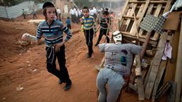 """Anak-anak Yahudi Ultra Ortodoks menyusun kayu dan boneka """"evil man"""" untuk dibakar saat perayaan hari Lag Ba'Omer di Bnei Brak, Israel (2/5). Tradisi ini merupakan peninggalan umat Yahudi sejak zaman Romawi. (AP Photo / Oded Balilty)"""