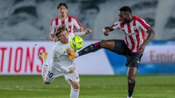 Gelandang Real Madrid, Luka Modric, berebut bola dengan pemain Athletic Bilbao, Inaki Williams, pada laga Liga Spanyol di Stadion Alfredo Di Stefano, Rabu (16/12/2020). Real Madrid menang dengan skor 3-1. (AP/Bernat Armangue)