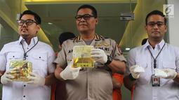 Kabid Humas Polda Metro Jaya, Kombes Pol Argo Yuwono (tengah)menunjukkan barang bukti beserta tersangka kasus narkotika jenis sabu di Polda Metro Jaya, Jakarta, Rabu (16/1). (Liputan6.com/Immanuel Antonius)