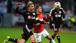 Gelandang Bayer Leverkusen Simon Rolfes (kiri) duel dengan bek Manchester United Chris Smalling pada pertandingan sepak  Liga Champions Grup A antara Bayern Leverkusen vs Manchester United di Leverkusen, Jerman Barat (281113). (AFP/Patrik Stollarz)