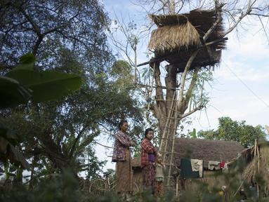 Warga berdiri di dekat sebuah rumah pohon di desa Taik Kyi, Myanmar, 14 Januari 2016. Warga di desa ini terpaksa membuat rumah pohon untuk tempat berlindung dari kawanan gajah liar yang belakangan ini kerap menyerang desa Taik Kyi. (AFP PHOTO/Ye Aung THU)